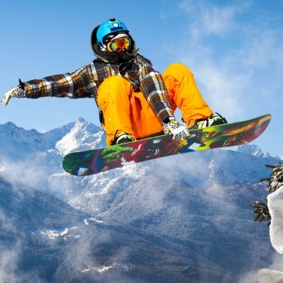 Snowboarder airbore with mountain in background