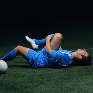 injured soccer player holding knee